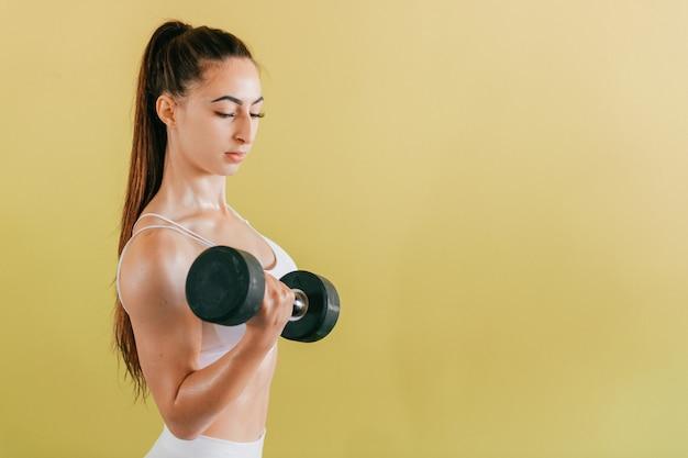 Athletische bodybuilderfrau mit dummköpfen. schönes brunettemädchen mit den muskeln, die gewichte auf gelber wand anheben.