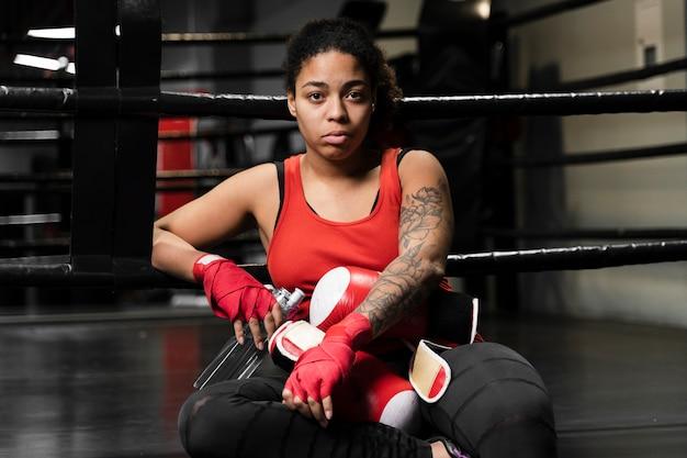 Athletische boxerfrau, die eine pause vom trainieren macht