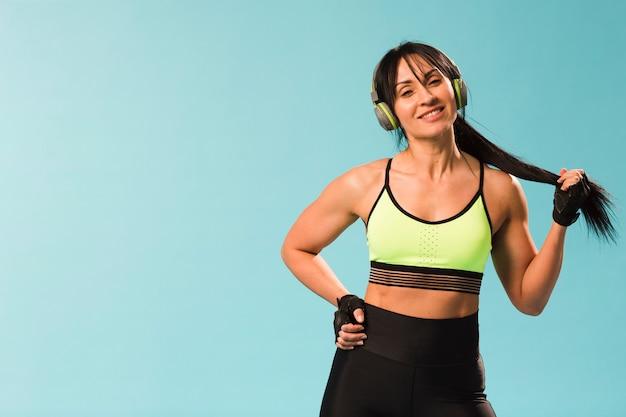 Athletische frau des smiley, die in der turnhallenausstattung mit kopfhörern aufwirft
