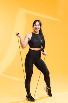 Athletische frau des smiley in der turnhallenausstattung mit springendem seil