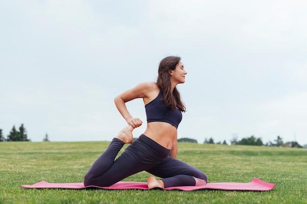 Athletische frau, die draußen yoga tut
