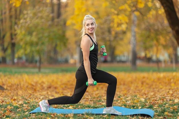 Athletische frau, die eignungsübungen in der natur tut