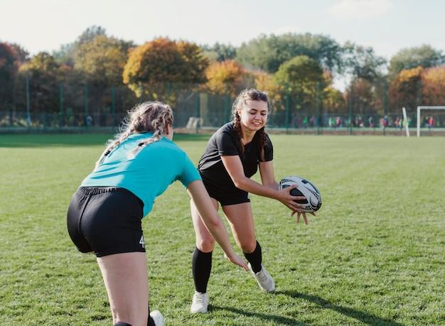Athletische frau, die einen rugbyball fängt