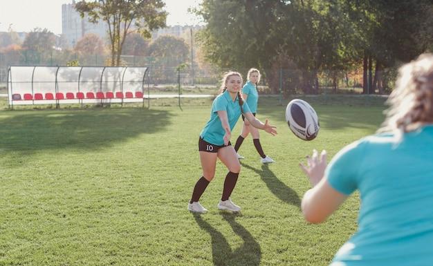 Athletische frau, die einen rugbyball führt