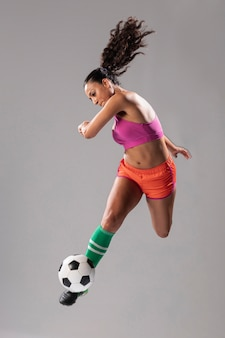 Athletische frau, die fußball tritt