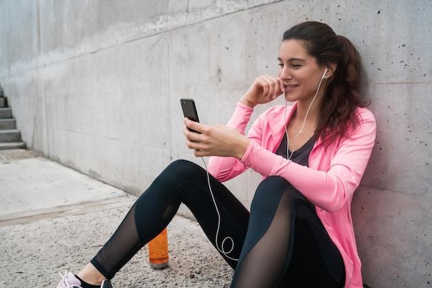 Athletische frau, die ihr telefon verwendet.