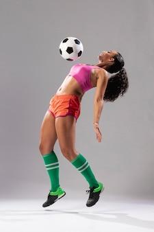 Athletische frau, die mit ball spielt
