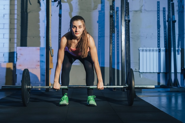 Athletische frau, die mit einem barbell in der turnhalle trainiert