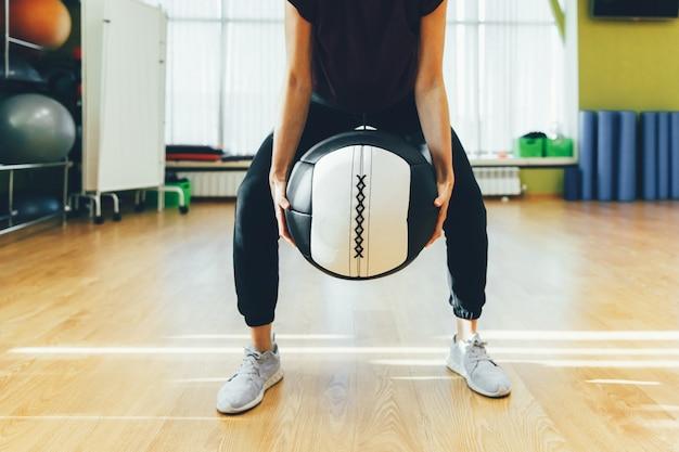 Athletische frau, die mit großem schwerem ball beim sein in der gedrungenen position trainiert. muskulöse frau, die passendes training des kreuzes an der turnhalle tut.