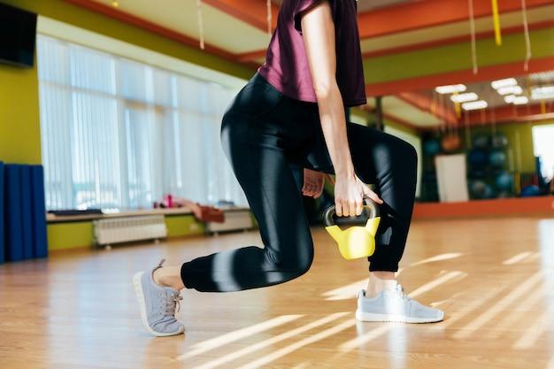Athletische frau, die mit kesselglocke beim sein in der gedrungenen position trainiert. muskulöse frau, die passendes training des kreuzes an der turnhalle tut.