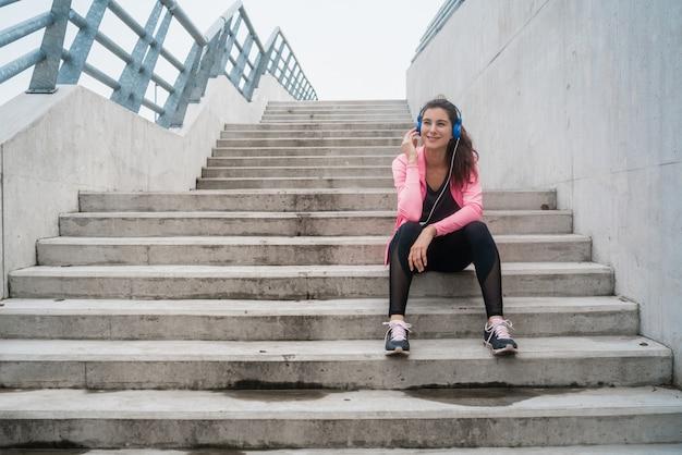 Athletische frau, die musik auf einer pause vom training hört.
