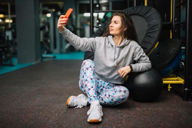 Athletische frau, die selfie auf smartphone in der turnhalle nimmt