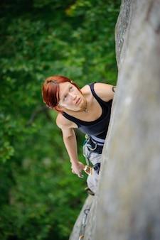 Athletische frau, die steile klippenwand in der sommerzeit klettert