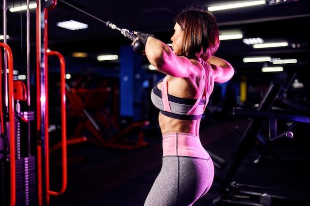 Athletische frau, die übung für rückseite, unter verwendung der maschine, in der turnhalle - hintere ansicht tut