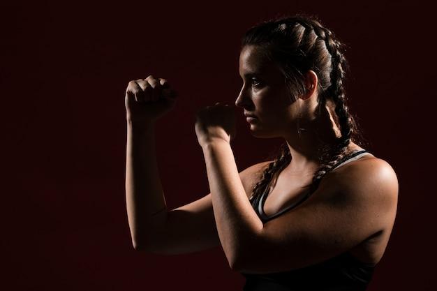 Athletische frau in der eignung kleidet auf dunklem hintergrund