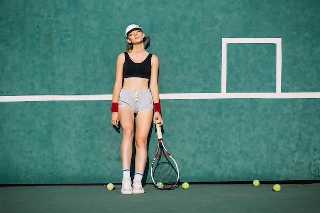Athletische frau in der sportkleidung auf einem tennisplatz