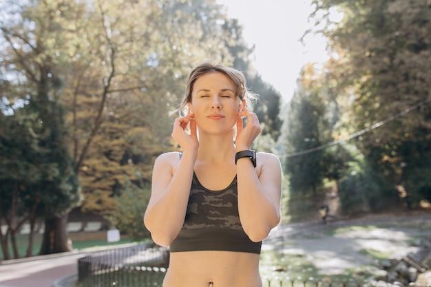 Athletische frau in tragenden kopfhörern hörend musik
