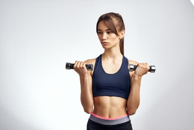 Athletische frau muskeltraining schlanke figur gymnastikgymnastik heller hintergrund
