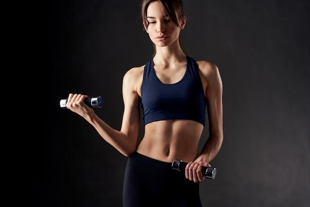 Athletische frau muskeltraining schlanke figur gymnastikraum dunklen hintergrund