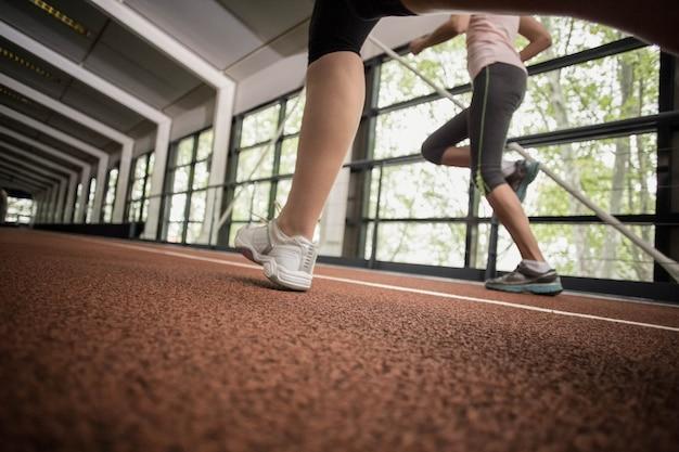 Athletische frauen, die auf laufbahn laufen