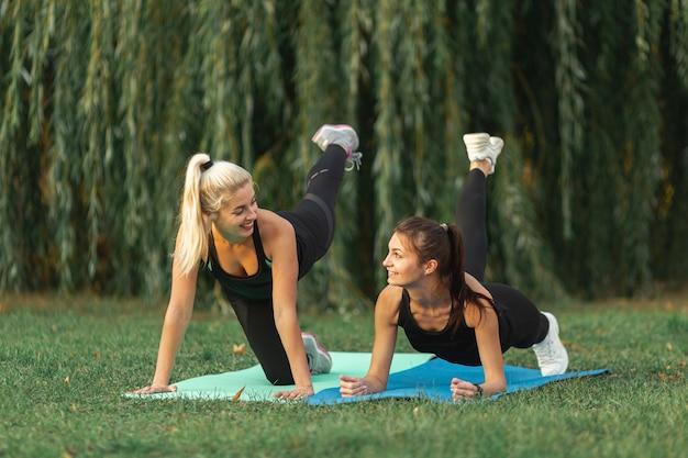 Athletische frauen, die draußen yogaübungen tun