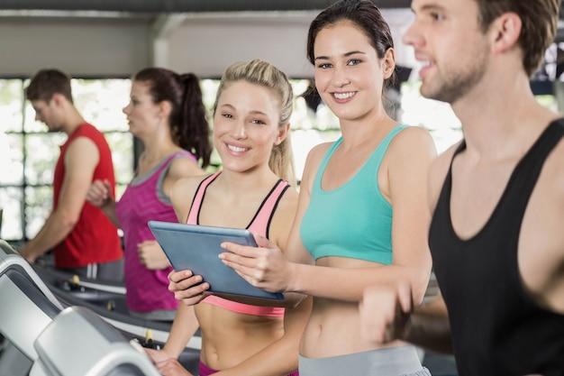 Athletische frauen, die tablette crossfit turnhalle betrachten