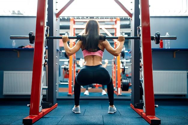 Athletische junge frau, die kreuzhebenübung in der smith-maschine tut