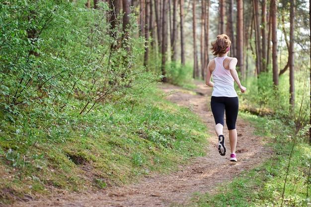 Athletische junge frau in den rosa turnschuhen lassen im frühjahr wald laufen