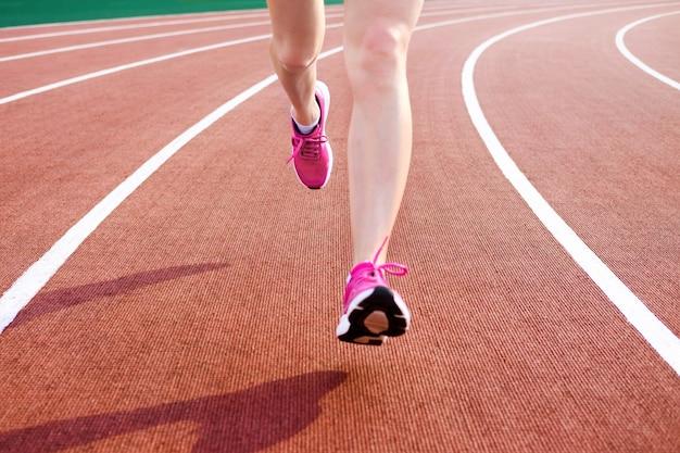 Athletische junge frau in den rosa turnschuhen laufen auf laufbahnstadion