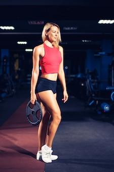 Athletische junge sexy eignungsfrau auf diätzug und trainieren in der turnhalle