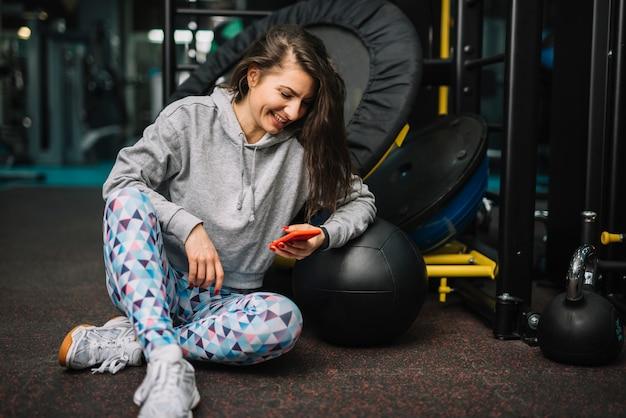 Athletische lächelnde frau mit smartphone in der turnhalle
