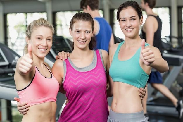 Athletische lächelnde frauen, die mit den daumen oben in der turnhalle aufwerfen