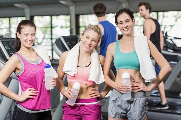Athletische lächelnde frauen, die mit flasche wasser in der turnhalle aufwerfen