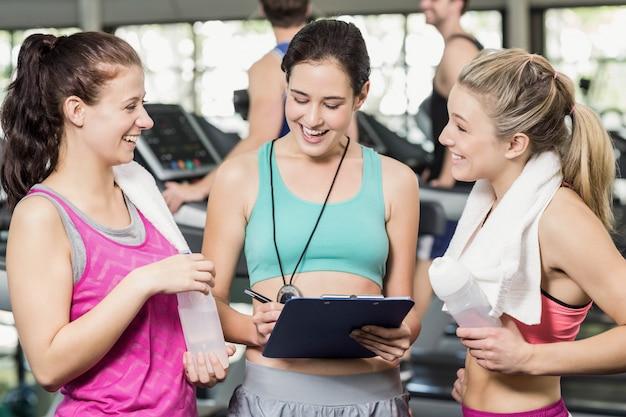 Athletische lächelnde frauen, die über leistung in der turnhalle sich besprechen