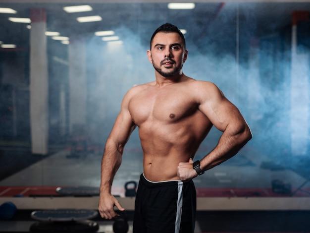 Athletische mannaufstellung, seine muskeln in der turnhalle vorführend