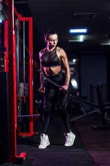 Athletische sexy frau, die übung unter verwendung der maschine in der turnhalle - seitenansicht tut