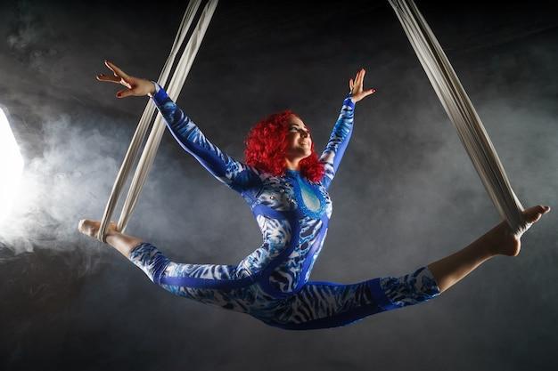 Athletische sexy luftzirkuskünstlerin mit rotschopf im blauen kostüm, die mit balance in der luft tanzt.