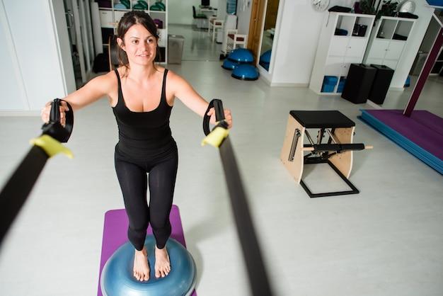 Athletische sitzfrau macht trx-übung
