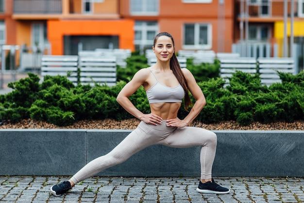 Athletische, sportive brunettefrau, die hockenübung im sonnigen park vor städtischen häusern tut.