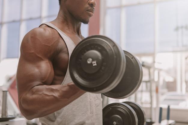 Athletischer afrikanischer mann, der mit dummköpfen an der turnhalle ausarbeitet