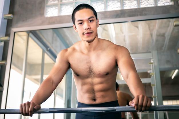 Athletischer asiatischer mann gepasst und gesundes lächeln in der turnhalle nach training.