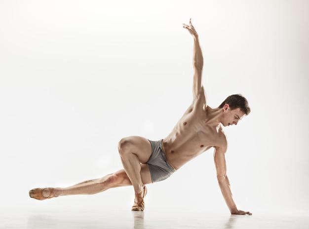 Athletischer balletttänzer in einer perfekten form, die auf dem weißen hintergrund lokalisiert wird. studioaufnahme. ballettkonzept