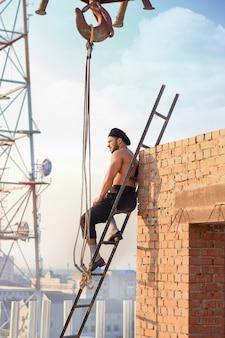 Athletischer baumeister mit nacktem oberkörper, der auf einer leiter hoch sitzt. mann lehnt sich an die mauer und schaut weg. extreme gebäude bei heißem wetter. kran und fernsehturm im hintergrund.