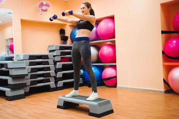 Athletischer frauentrainer, der aerobe klasse mit steppern tut. sport