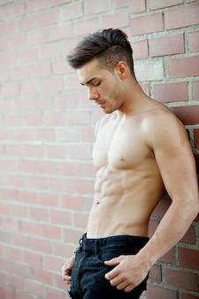 Athletischer hemdloser junger mann des hübschen sitzes