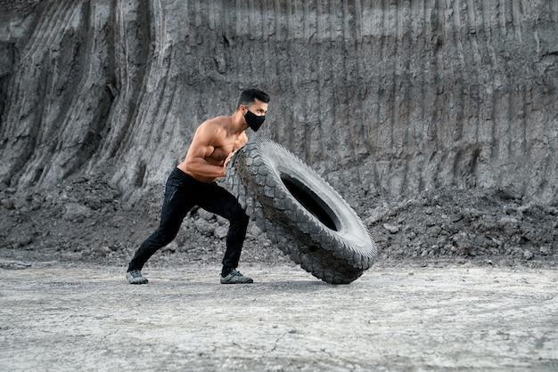 Athletischer hemdloser mann in der medizinischen schwarzen maske, die großen schweren reifen am sandkasten schiebt. konzept des bodybuildings und des trainings im freien.