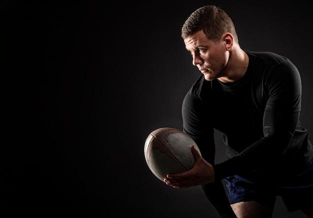Athletischer hübscher männlicher rugbyspieler, der ball mit kopienraum hält