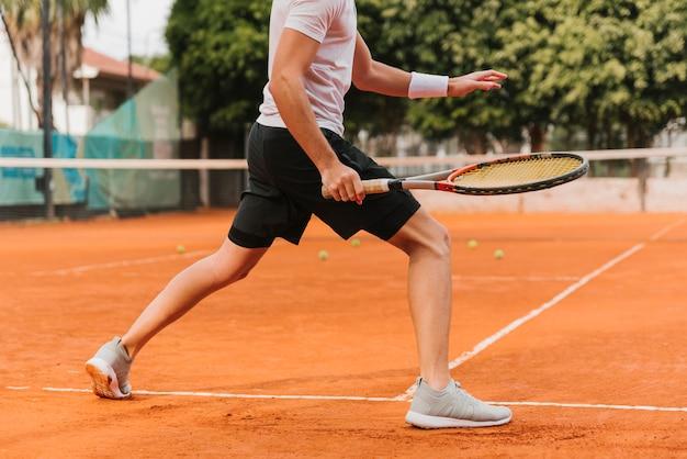 Athletischer junge, der tennis spielt