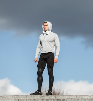 Athletischer junger mann, der draußen mode aufwirft
