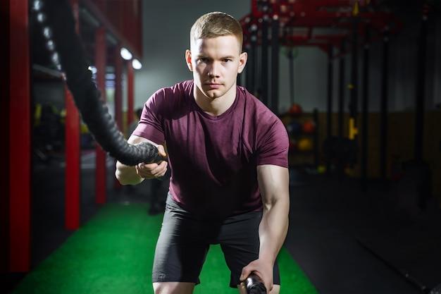 Athletischer junger mann mit dem kampfseil, das übung in der funktionstrainingseignungsturnhalle tut